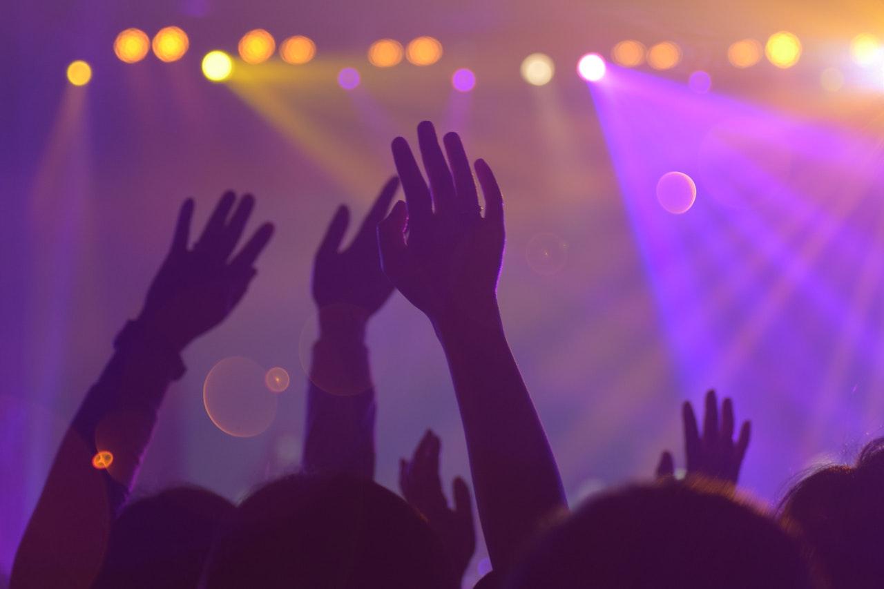 Dettaglio mani al cielo durante festa 18 anni in locale notturno