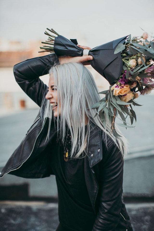 Ragazza con mazzo di fiori che scherza su invito festa