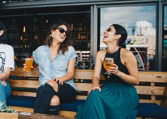 Ragazze ridono in locale estivo sedute su panchina