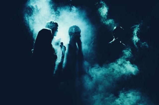 Ombre ragazzi in luci soffuse all'interno di un locale